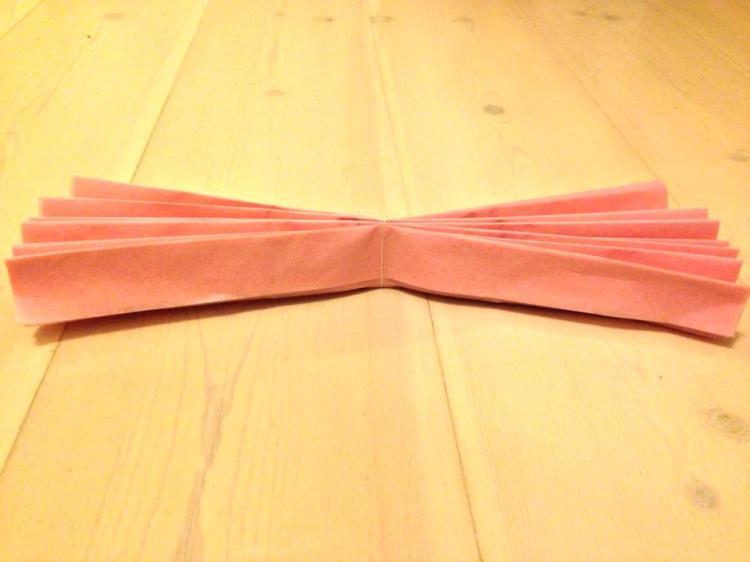 Sido lanka napakasti taitoksen keskikohtaa. Jos haluat laittaa pompomit riippumaan, kannattaa lankaa jättää silloin riittävästi yli, jotta saat tehtyä langasta ripustus lenkin.